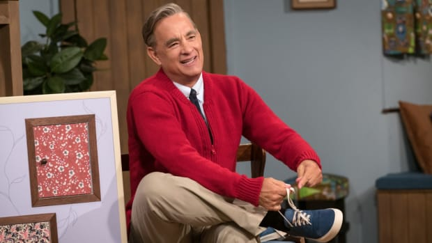 a-beautiful-day-in-the-neighborhood-tom-hanks-fred-rogers-tying-shoe-red-sweater