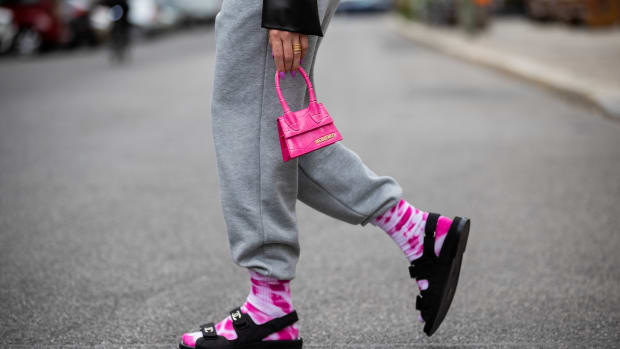 woman-wearing-grey-sweatpants-with-tie-dye-socks-chanel-sandals-pink-mini-jacquemus-bag