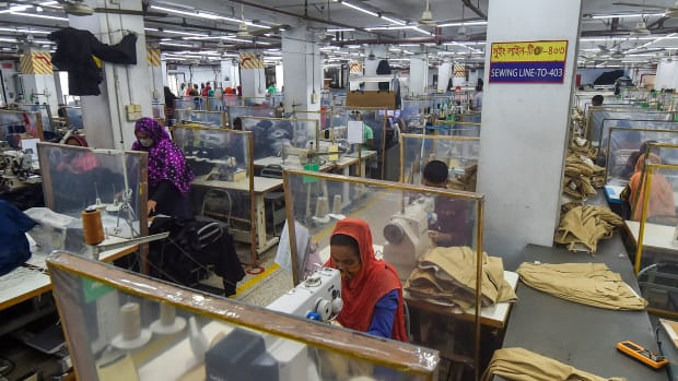 Labourers work at their stations separated by partitions as a preventive measure against the Covid-19 coronavirus at the Civil Engineers Limited garments factory in Dhaka