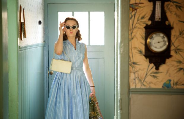 Eilis in a blue dress, statement sunglasses and a recyclable shopping bag. (That's so 2015.) Photo: Kerry Brown/Twentieth Century Fox Film Corporation