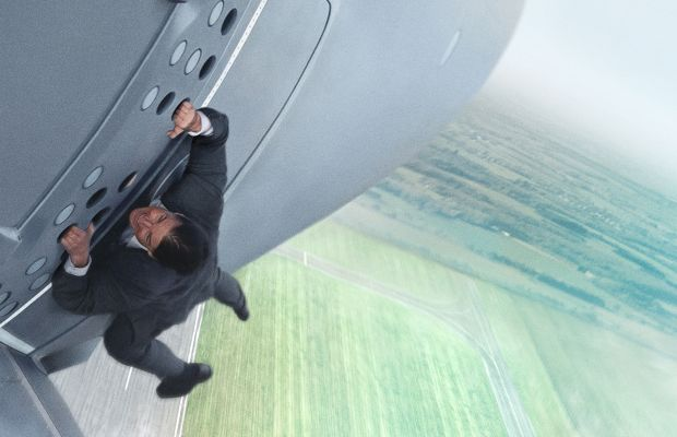 Tom Cruise hanging off an airplane in a bespoke suit. As one does. Photo: Bo Bridges/Paramount Pictures