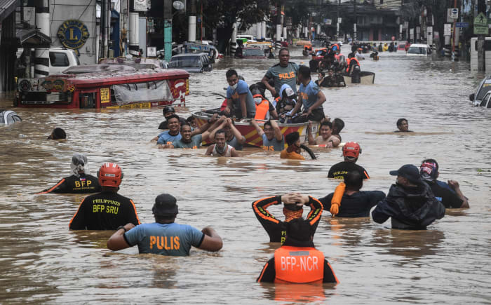 Rescuers pull a rubber boat carrying residents through a flooded street after Typhoon Ulysses hit Marikina on November 12, 2020.