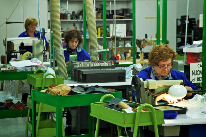 Employees use machines to manufacture footwear at a factory in Corridonia, Italy.