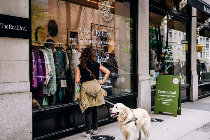 A customer waits to enter The RealReal store on Madison Avenue in New York City in September 2020.