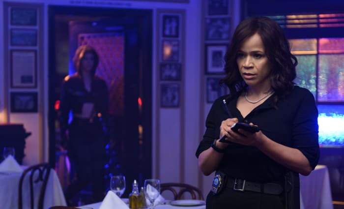 Detective Renee Montoya surveys the scene while Huntress (left) lurks in the doorway.