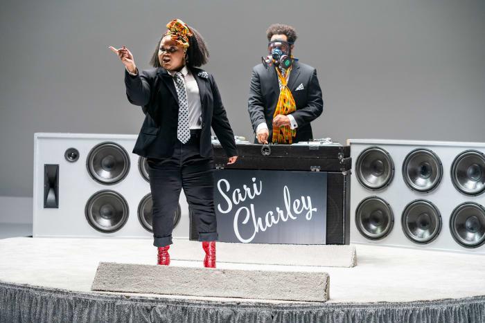 Zuri Salahuddin canta 'Add Some Kente', enquanto Riddle, em sua máscara de gás personalizada, DJs.