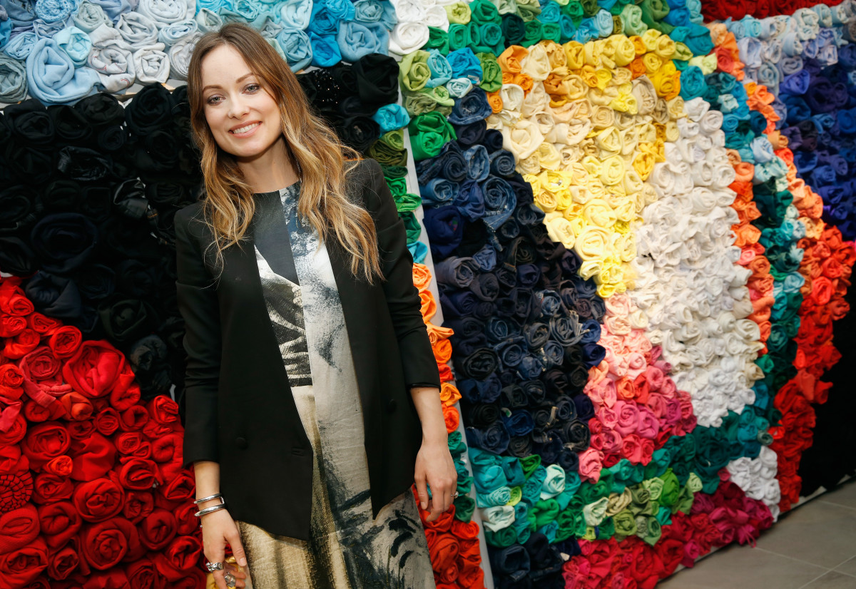 Olivia Wilde poses in front of a decorative wall of recycled T-shirts. Photo: Brian Ach/Getty Images