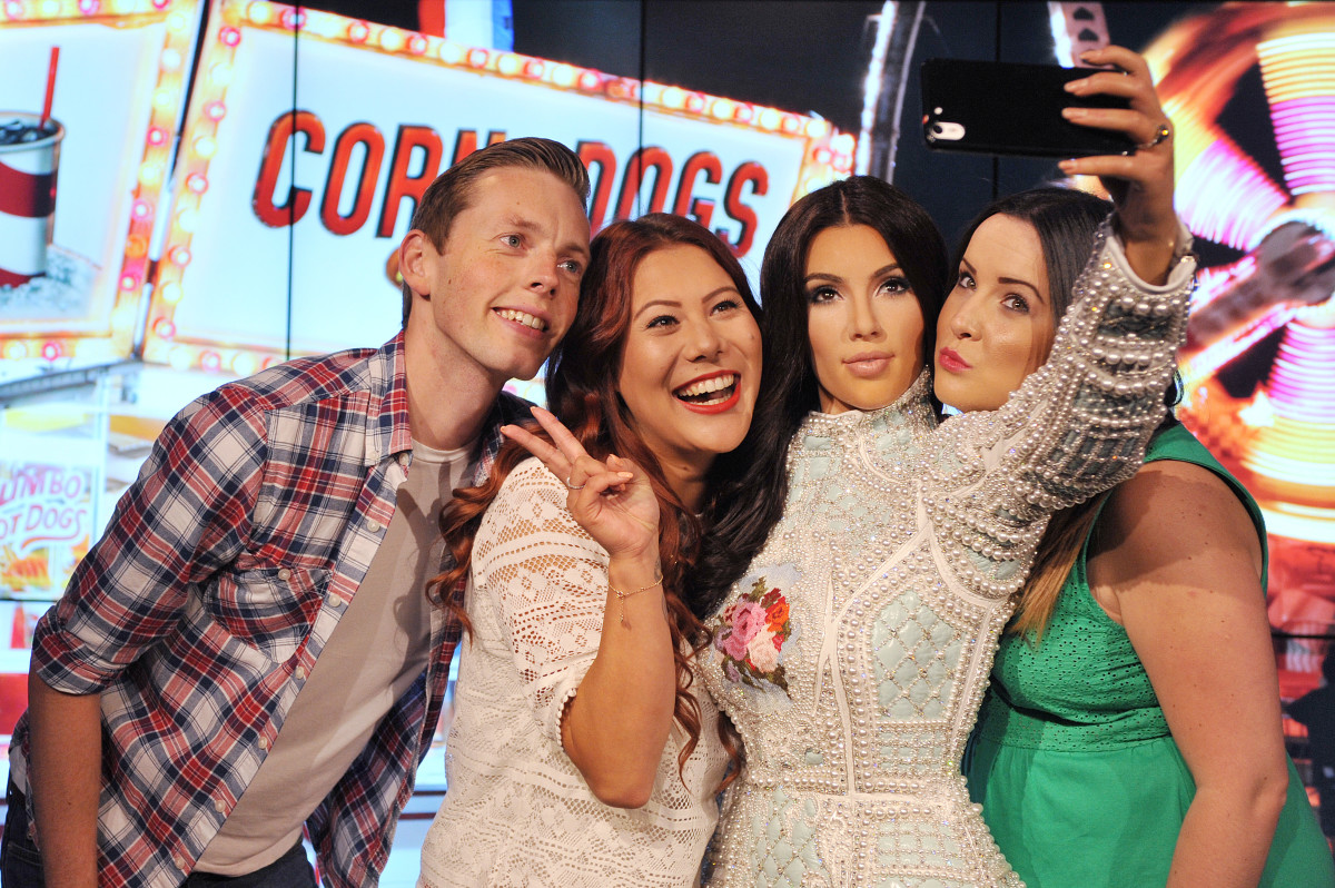 Fans posing with Kim Kardashian's Madame Tussauds wax figure in London. Photo: Tabatha Fireman/Getty Images