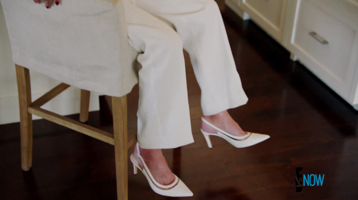 The camera lingers on Jenner's white pumps. Screengrab: E!