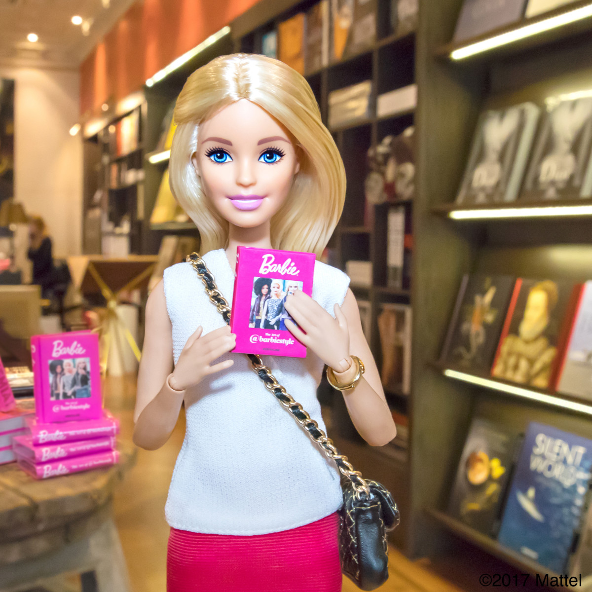 """Barbie with a copy of her new book, """"The Art of @barbiestyle."""" Photo: Courtesy"""