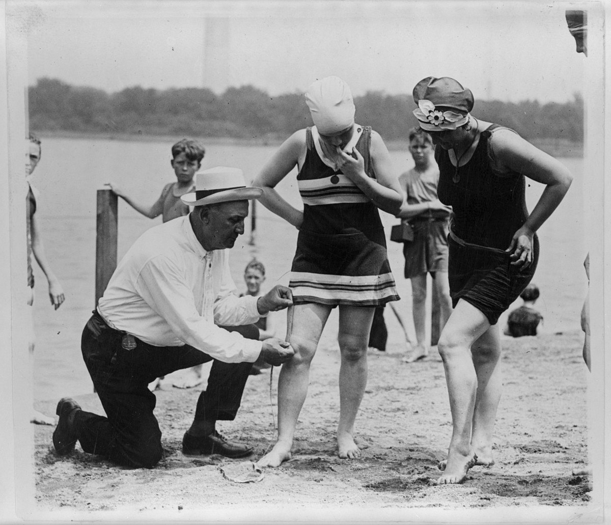 "Bill Norton, a bathing beach ""cop,"" measures the distance between the hem of a woman's swimsuit and her knee on a Washington, D.C., beach in 1922. Photo: Library of Congress"