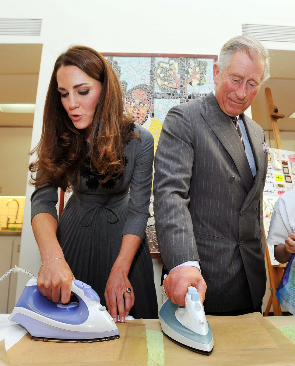 The Duchess of Cambridge, aka Kate Middleton, and Prince Charles show off their ironing techniques during a charity event. Photo: John Stillwell/WPA Pool/Getty Images