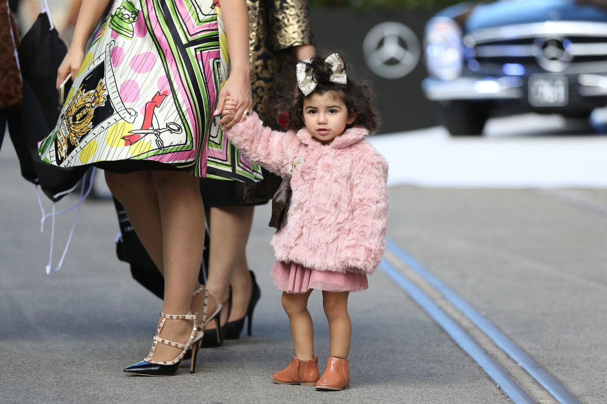 A tiny human wearing pink, a Chanel brooch and a Louis Vuitton bag at Mercedes-Benz Fashion Week in Sydney, Australia. Photo: Caroline McCredie/Getty Images