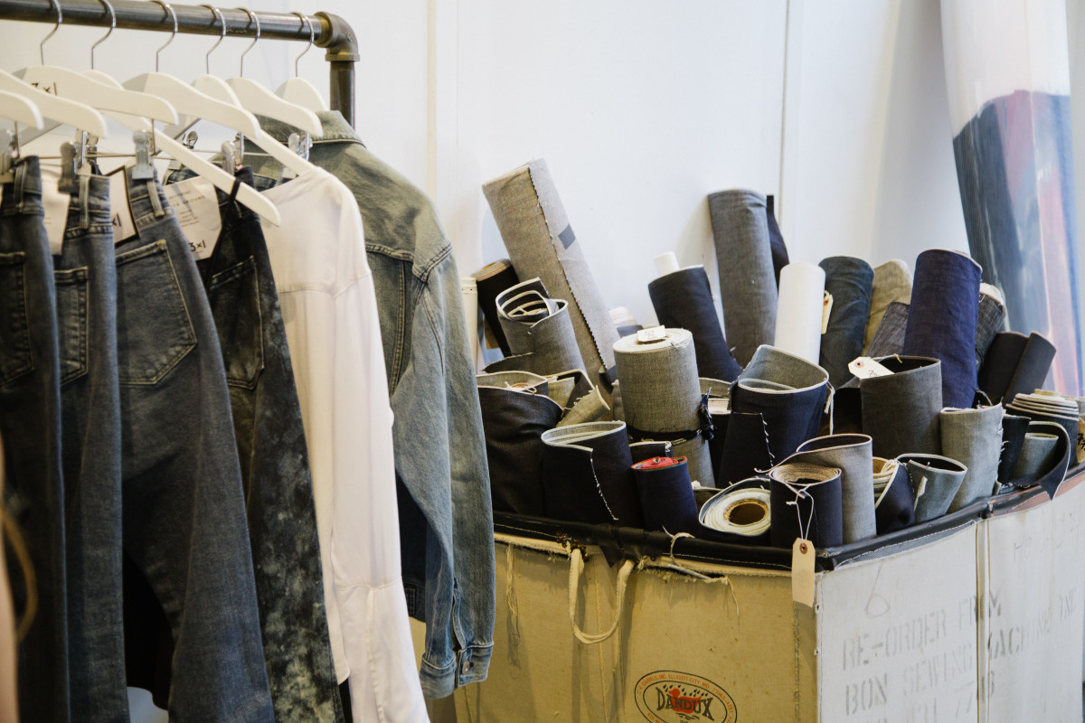 Rolls of selvedge denim next to a rack of ready-to-purchase 3x1 pieces. Photo: Whitney Bauck/Fashionista