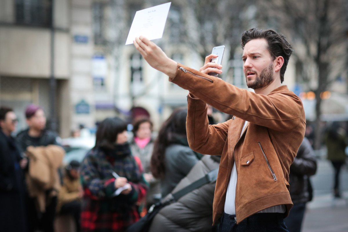 A showgoer taking a picture of his invitation during Paris Fashion Week. Photo: Edward Berthelot/Getty Images