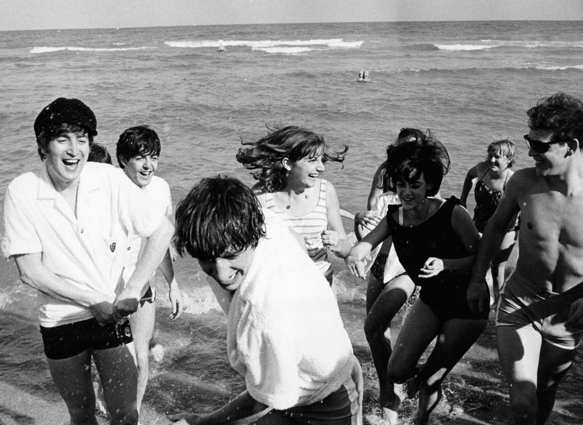 The Beatles on a beach in Miami, Fla., surrounded by female fans, circa February 1964. Photo: Daily Express/Archive Photos/Getty Images
