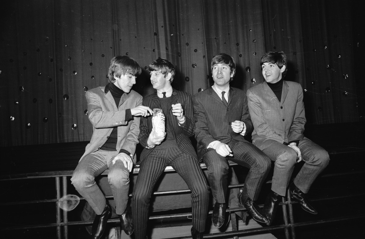 The Beatles (George Harrison, Ringo Starr, John Lennon and Paul McCartney) splitting a bag of popcorn at London's Lewisham Theatre in 1963. Photo: Terry Fincher/Express/Getty Images