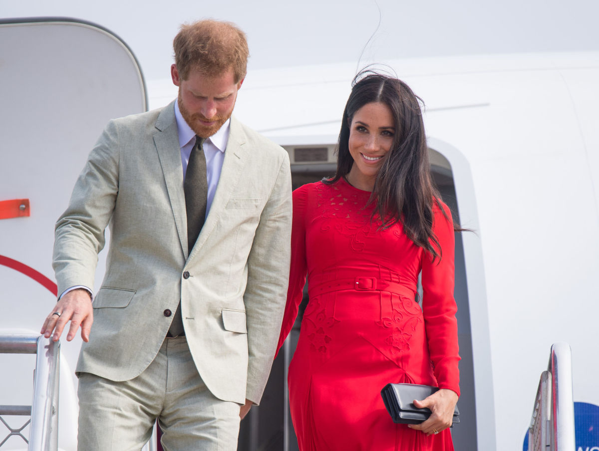 Prince Harry and Meghan Markle (in Self-Portrait) arrive at Fau'amotu Airport in Tonga. Photo:  Dominic Lipinski - Pool/Getty Images