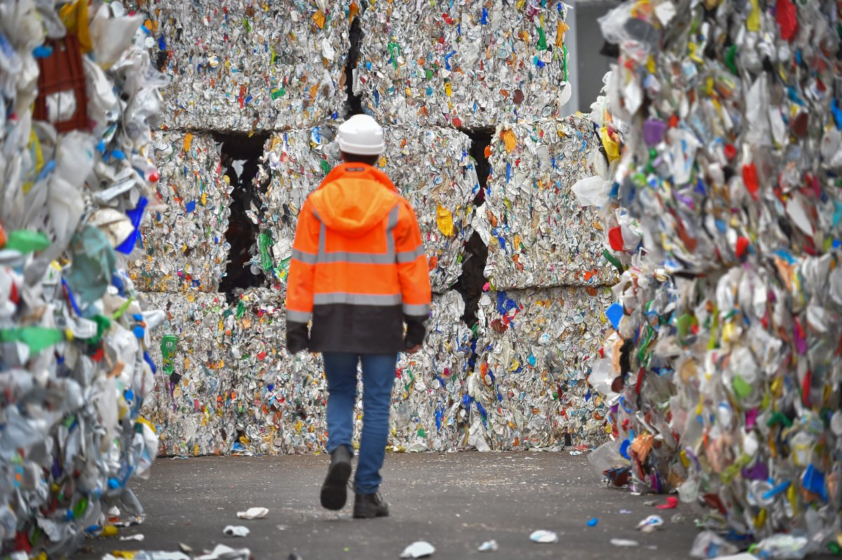 An employee walks through plastic waste waiting to be recycled at a sorting center in France. Photo: Loic Venance/AFP/Getty Images