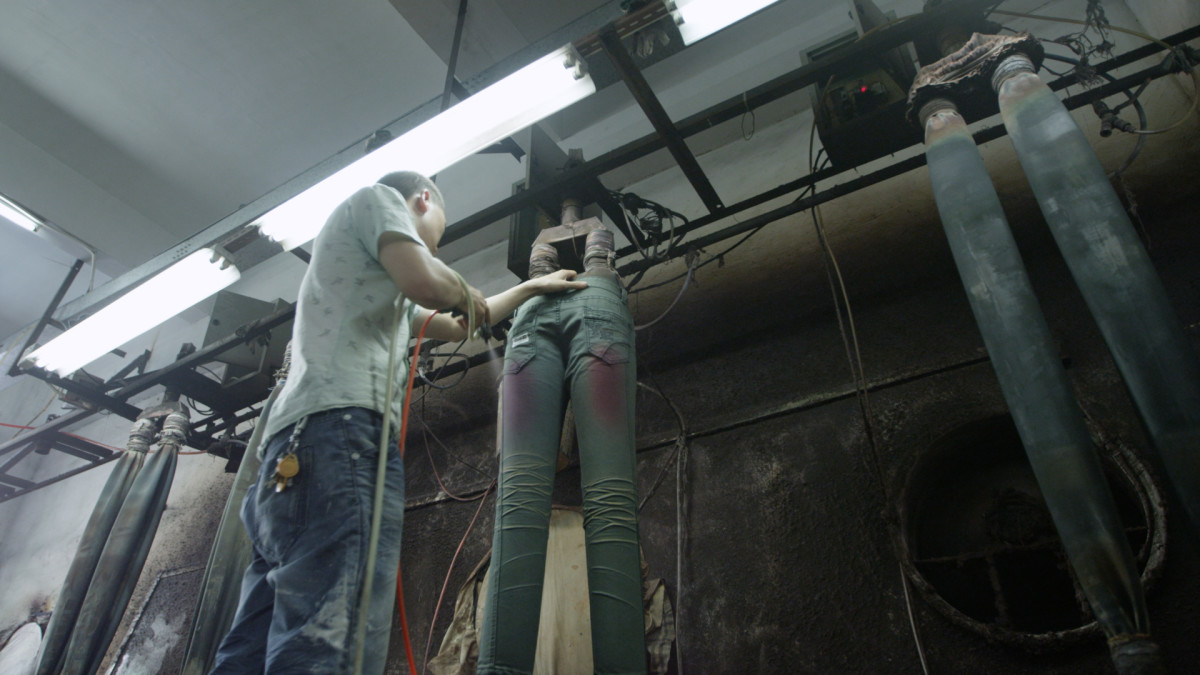 Spraying chemicals on jeans to produce the appearance of distressing. Photo: RiverBlue