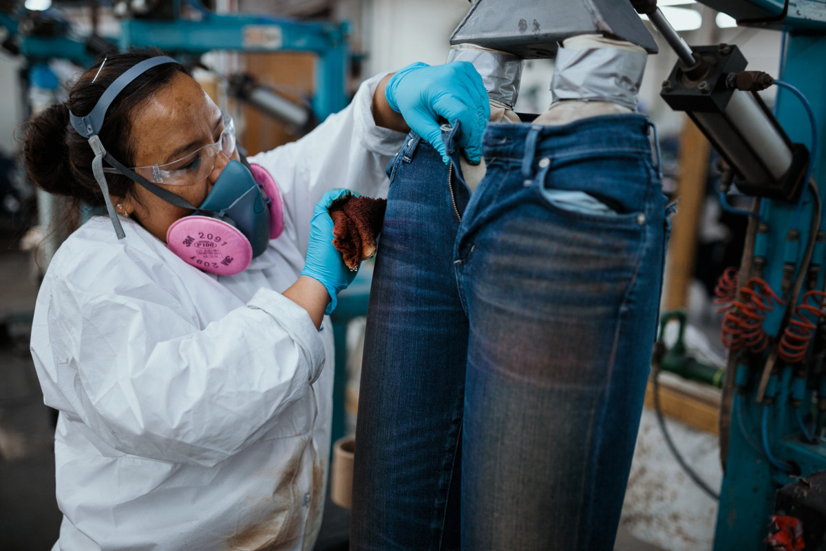 An employee lightening parts of jeans by hand. Photo: Jacob Boll/Fashionista