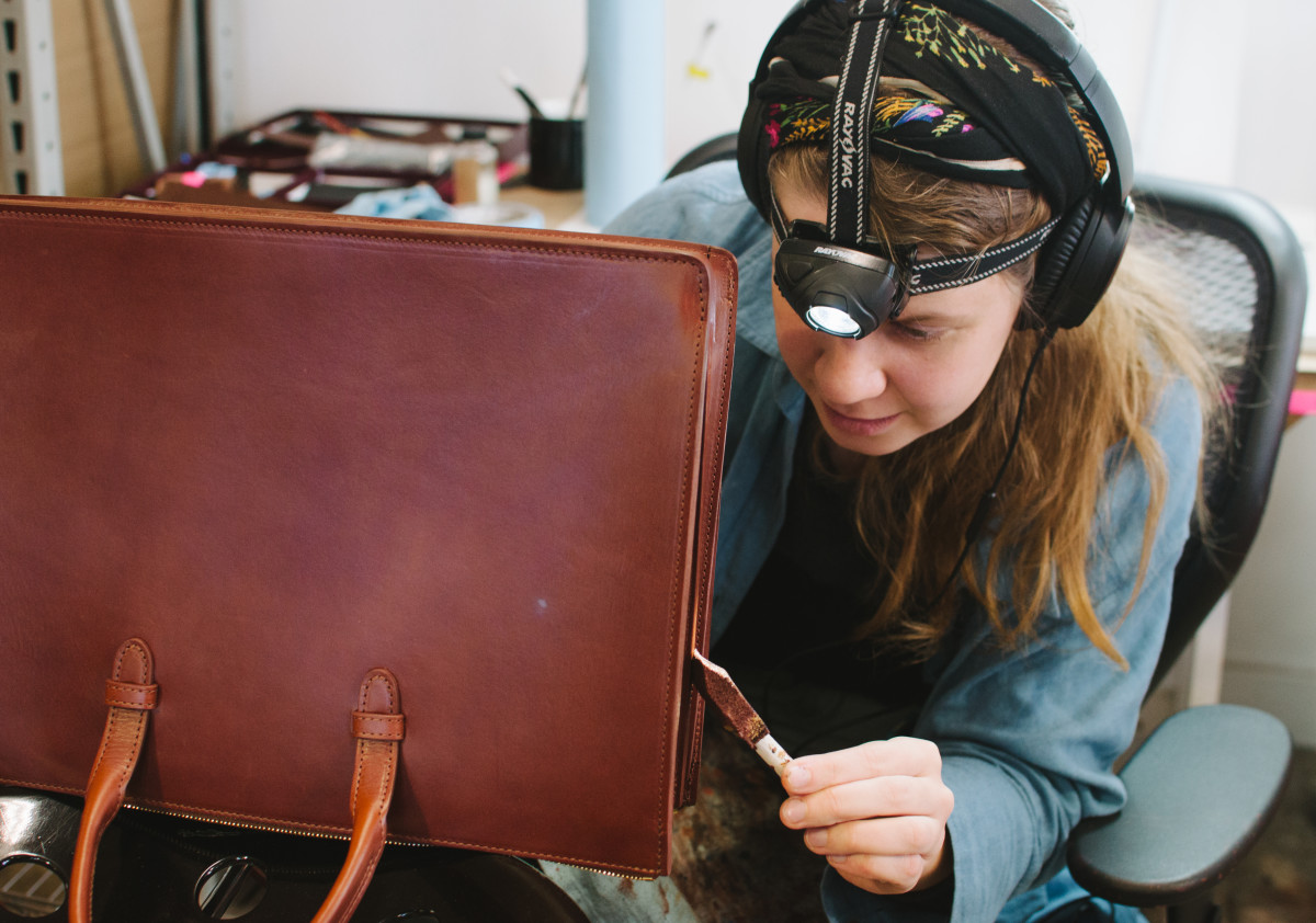 A Lotuff employee carefully paints and seals the edges of a partially-finished bag. Photo: Whitney Bauck/Fashionista
