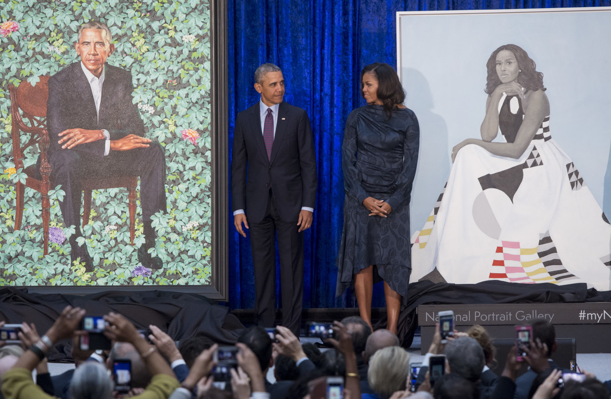 Former President Barack Obama and First Lady Michelle Obama stand beside their portraits by Kehinde Wiley and Amy Sherald after their unveiling. Photo: Saul Loeb/AFP/Getty Images