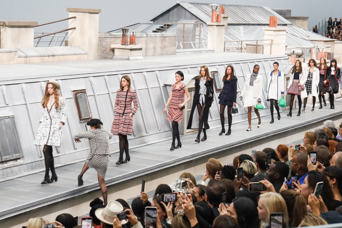 A woman from the audience climbs the runway to walk with the models during the finale of the Chanel Spring 2020 show. Photo: Victor Boyko/Getty Images