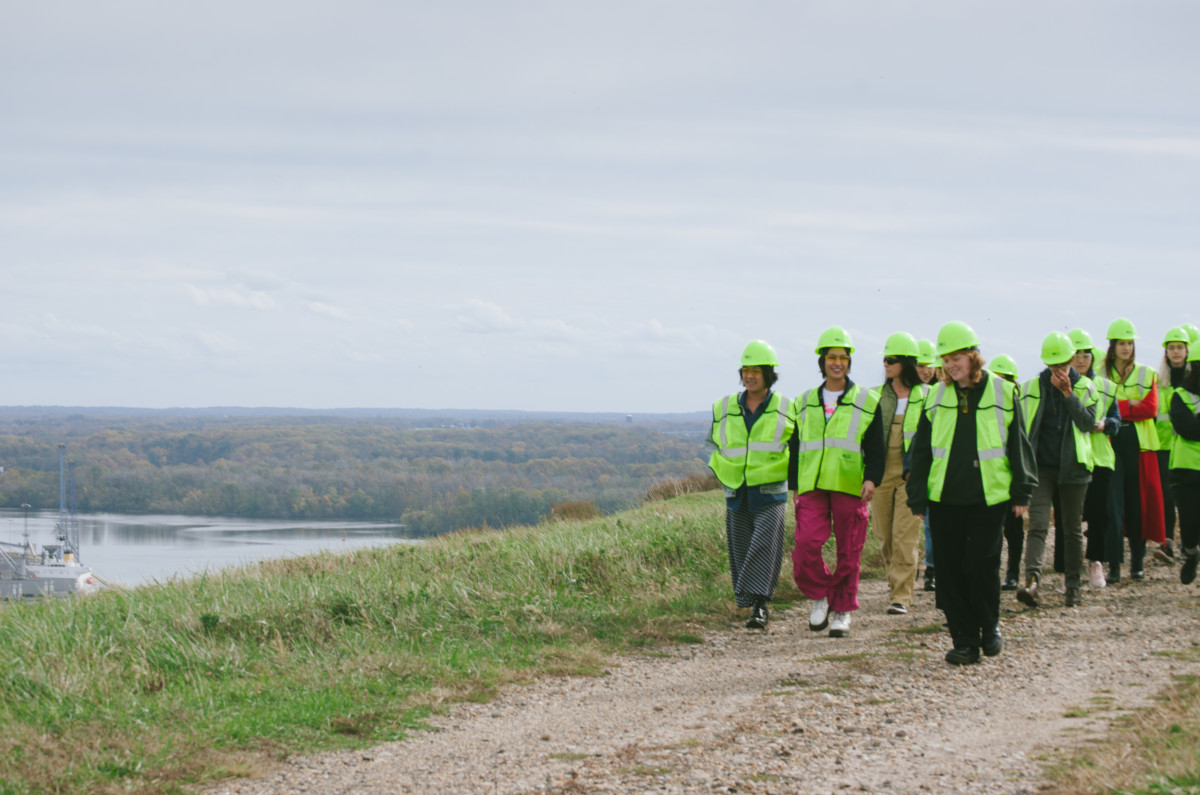 Students, clad in safety vests and hats, disembark from their tour bus at the top of a closed landfill. Photo: Whitney Bauck/Fashionista