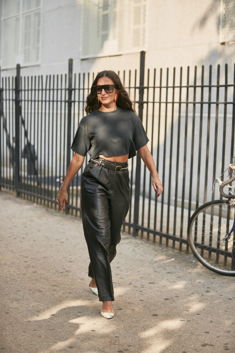 a woman wearing leather pants with a grey crop top during fashion week