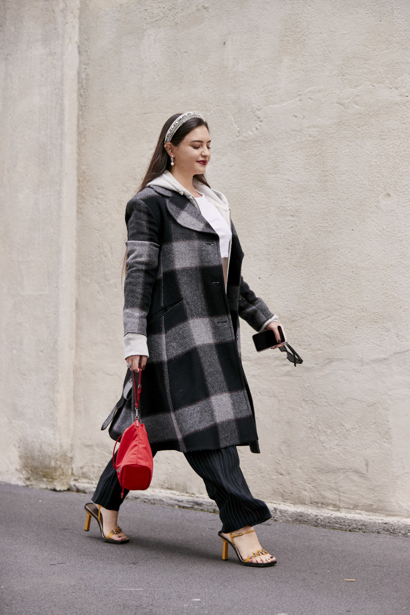 a woman wearing a headband, checked coat, striped trousers, and strappy sandals at milan fashion week