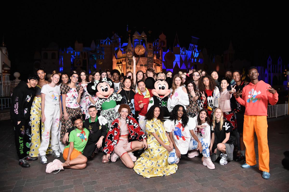 Os designers com Mickey e Minnie Mouse, além de todos os modelos após o show, comemoram a coleção da Cerimônia de Abertura em homenagem ao 90º aniversário do Mickey em Anaheim, Califórnia.