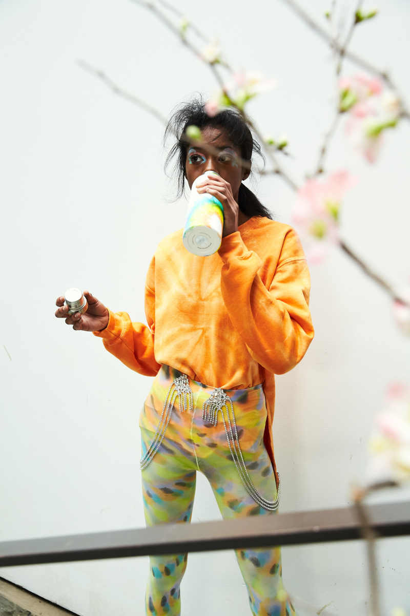 A model backstage at Collina Strada's Fall 2019 show drinking from a reusable water bottle painted to match her outfit. Photo: Soraya Zaman/Courtesy of Collina Strada