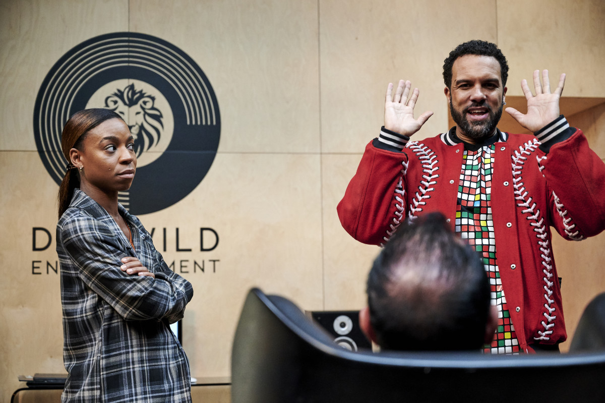 Stats whiz Tamzin (Pippa Bennett Warner) in her 'librarian' aesthetic, Don Wild (Christopher Meloni, seated) and Maxxx (O-T Fagbenle) in his trusty KTZ bomber.