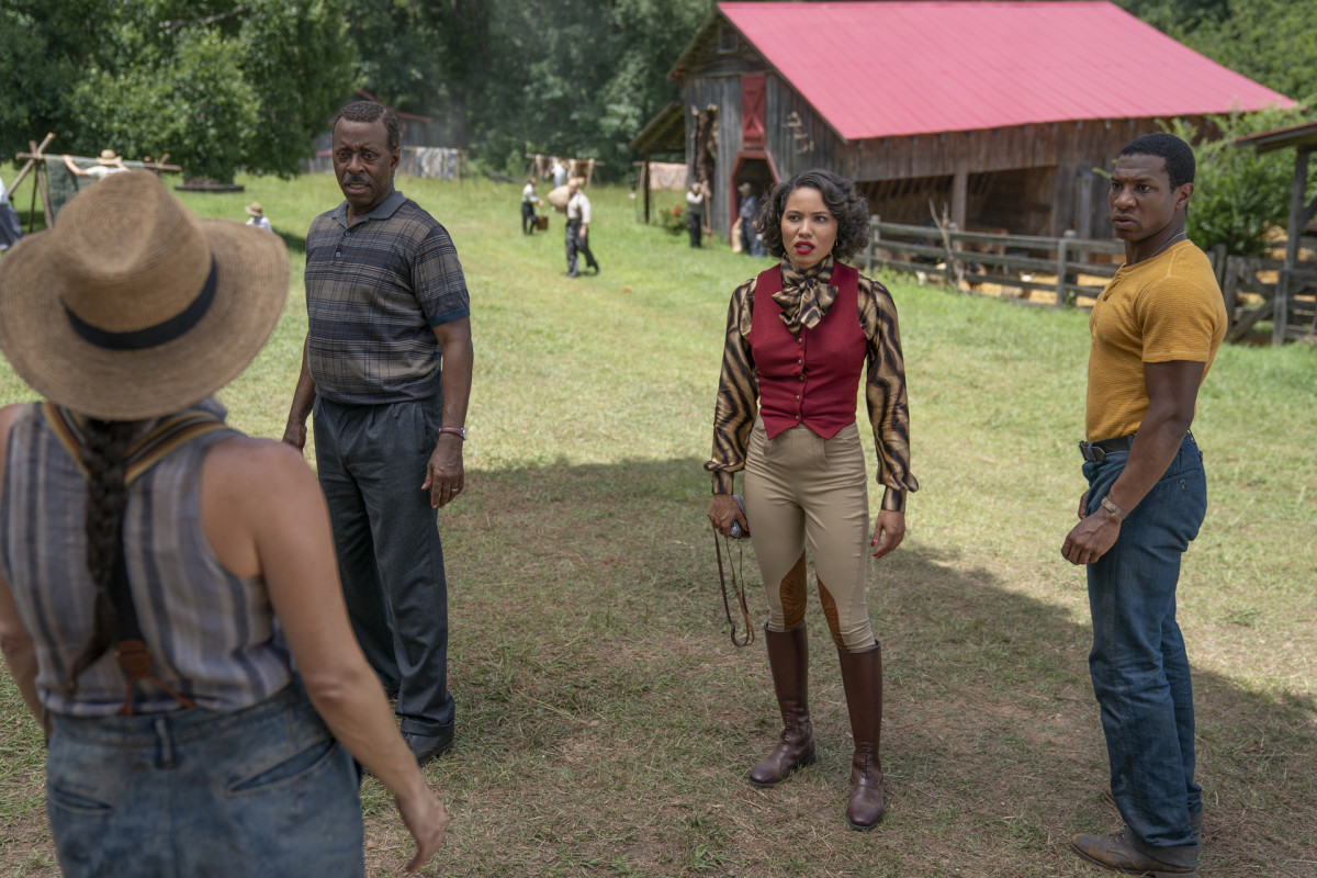 L–R: Uncle George (Courtney B. Vance), Leti and Tic (Jonathan Majors) mingle with the locals in Ardham.