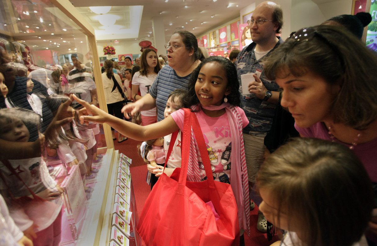 A young girl picks her new doll at the American Girl store in McLean, Va. in June 2011.