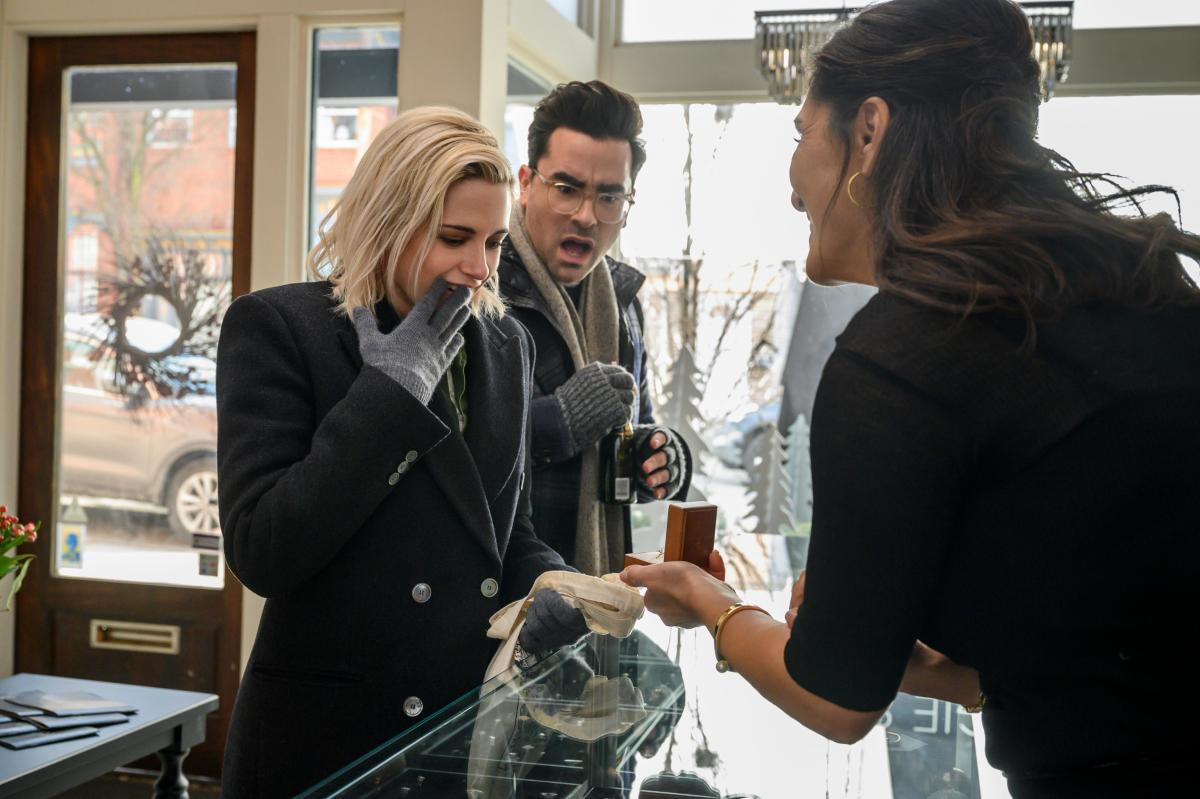 Abby (Kristen Stewart), in her Theory coat, surprises John (Dan Levy) with her holiday plans.