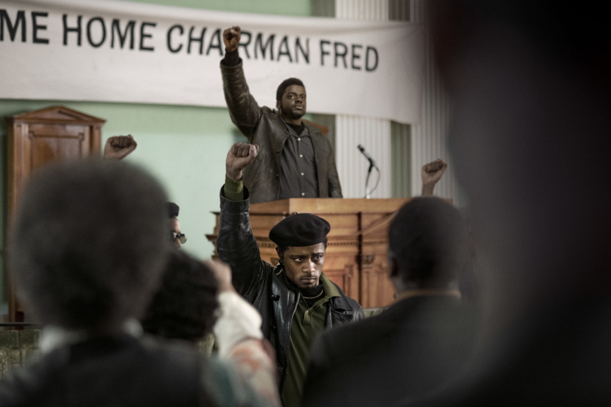 """William """"Bill"""" O'Neal (Lakeith Stanfield, center front) and Chairman Fred at the podium."""