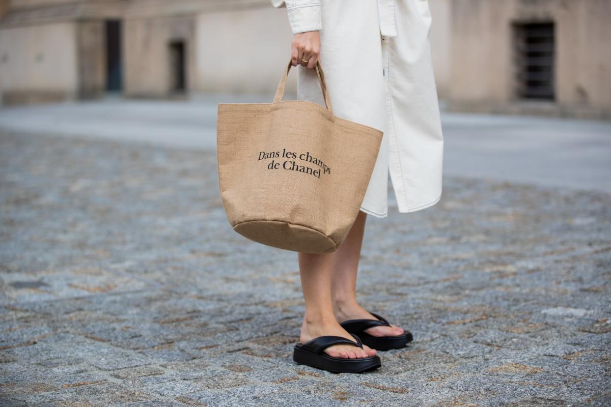 Swantje Soemmer is seen wearing white dress Blanche, Arket plateau flip flops, Chanel beach bag on July 07, 2020