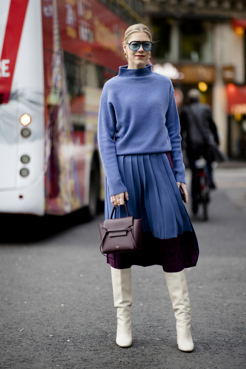 A showgoer wearing a Classic Blue sweater and skirt.