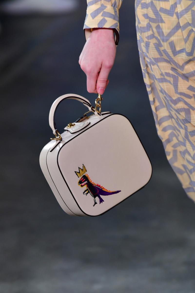 "A model carrying a Coach Fall 2020 bag featuring Jean-Michel Basquiat's ""Pez Dispenser""."