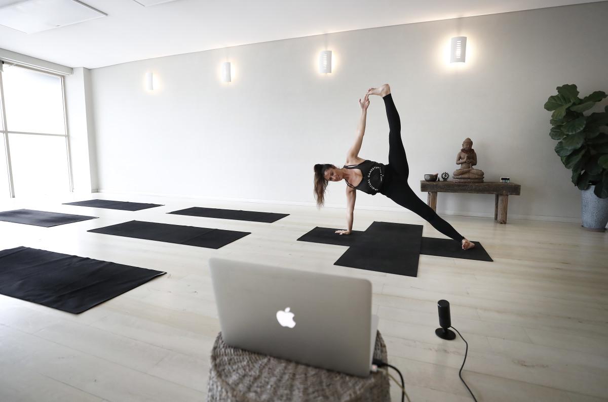 Yoga instructor Asha Elliott conducts a live stream class in Australia.