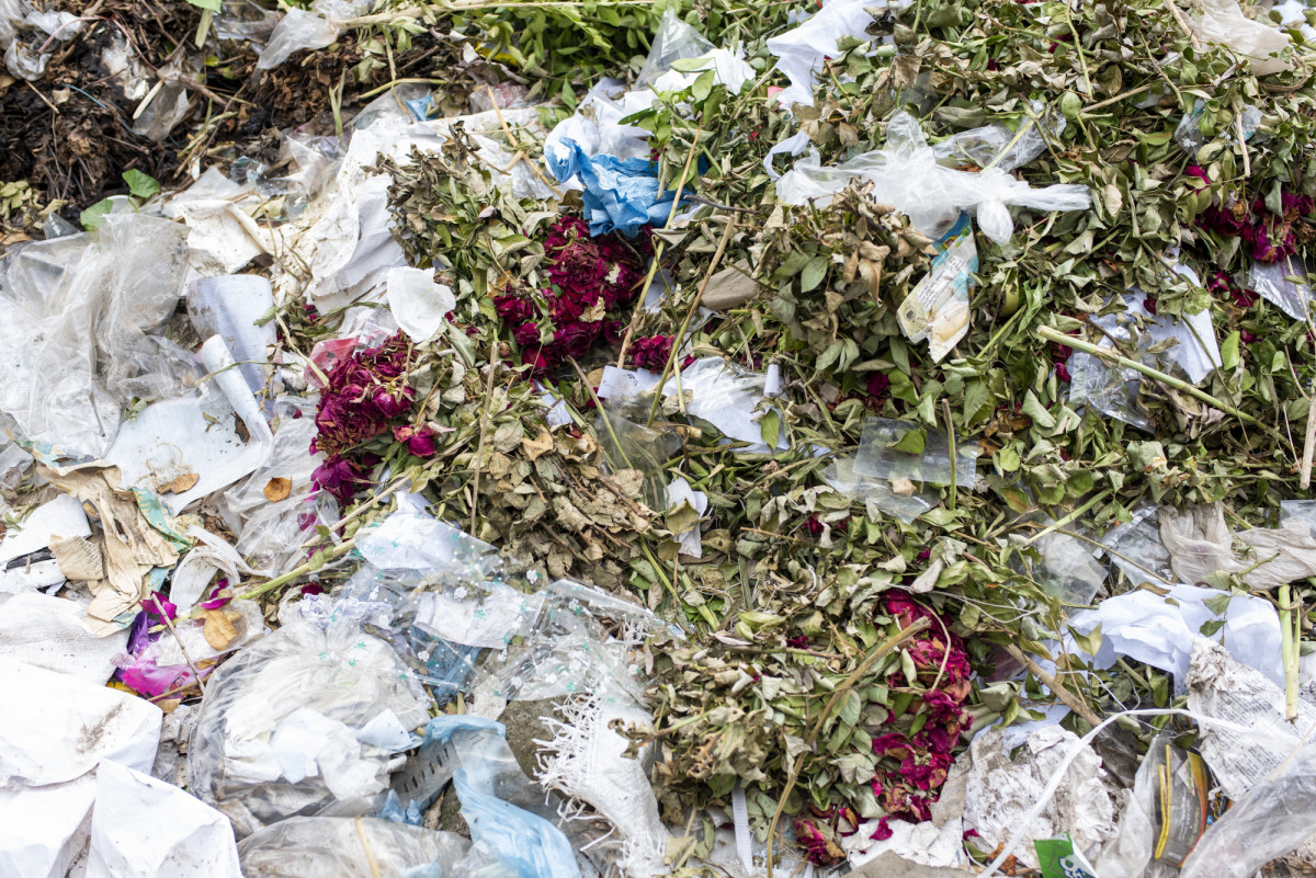 A pile of dried flowers from the previous year's memorial at the Rana Plaza memorial site. These were likely left by family members of the victims.