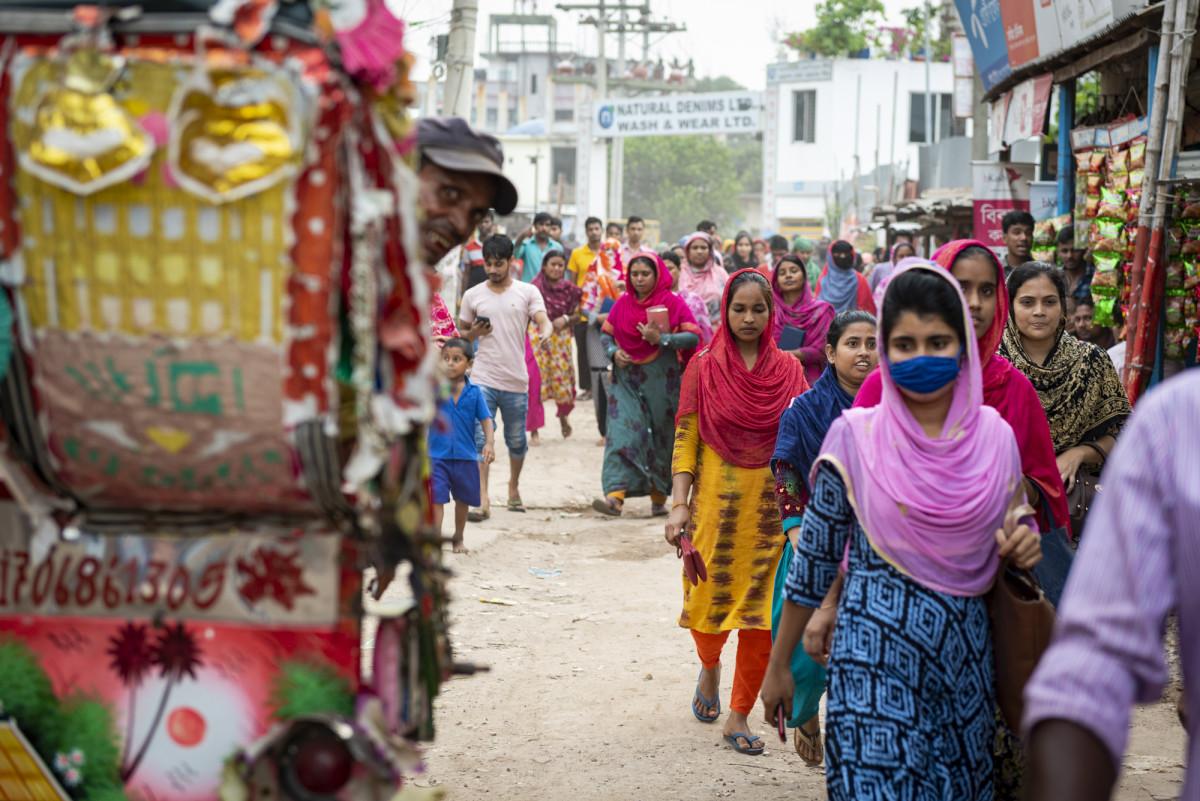 Um mar de mulheres que saem de uma fábrica de roupas depois que o turno termina em uma fábrica de jeans.