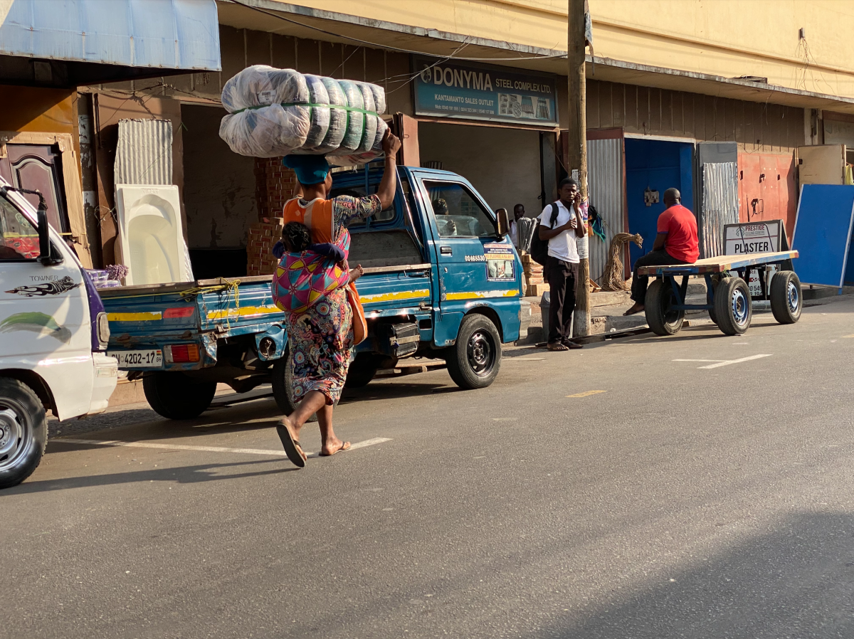 A kayayo carrying a bale of secondhand clothing on her head and a baby on her back through Accra.