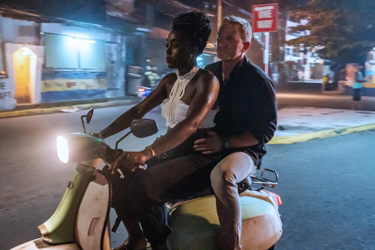 Nomi (Lashanna Lynch) takes Bond (Daniel Craig) for a ride.