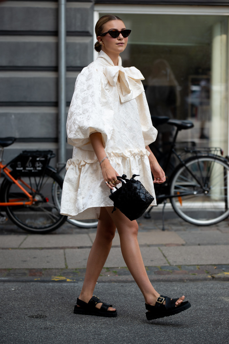 Maren Schia wearing ivory dress, sunglasses, black bag and black sandals outside Malaikaraiss during Copenhagen fashion week SS21