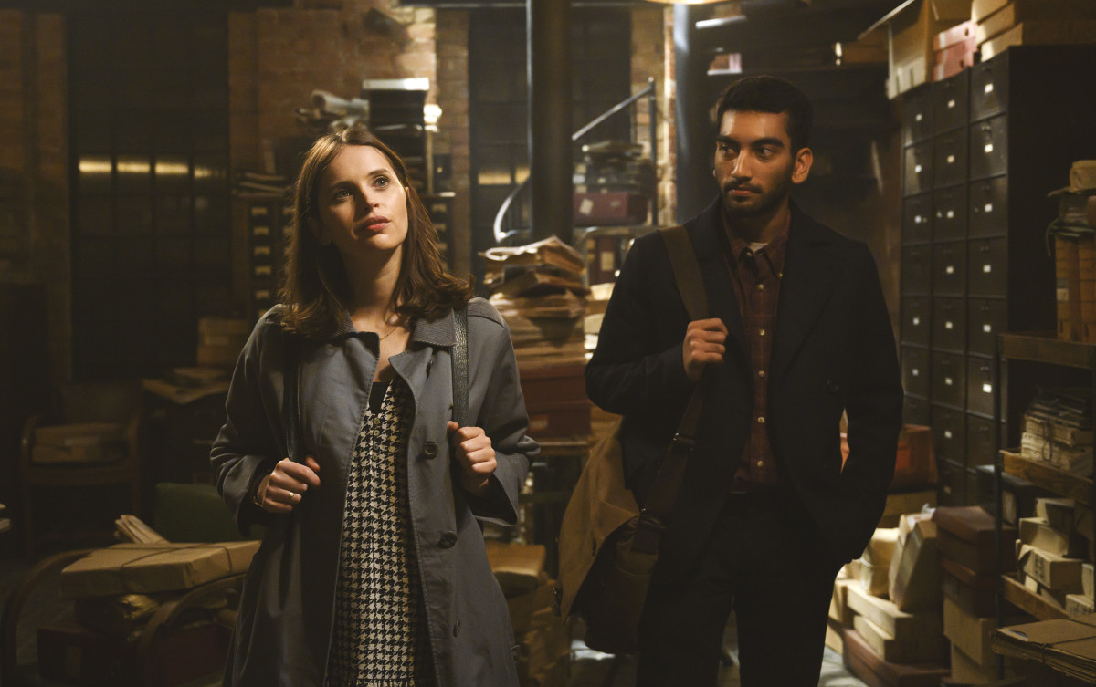 Ellie (Felicity Jones), in Jennifer-reminiscent houndstooth and '60s Burberry jacket, and Rory (Nabhaan Rizwan).